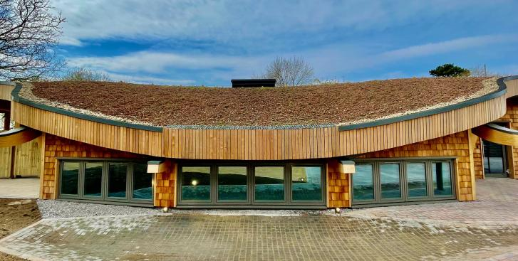 Earth Lab facility showcasing natural building materials and wildflower roof